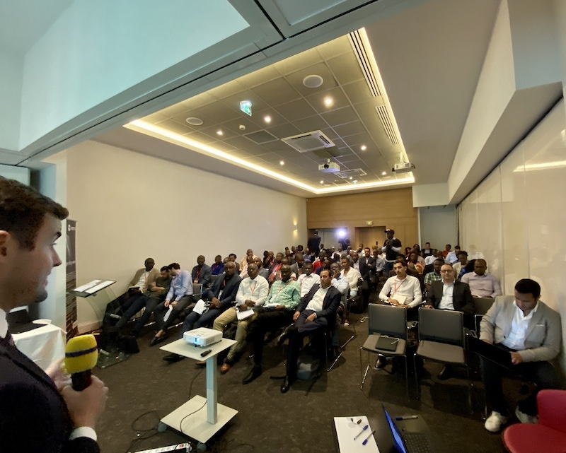 shows a speaker presenting to a roomful of people