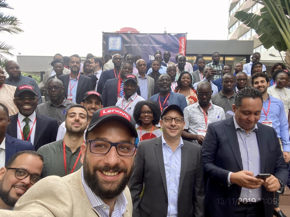 shows a selfie photo taken by a man in the foreground, with tens of people behind him