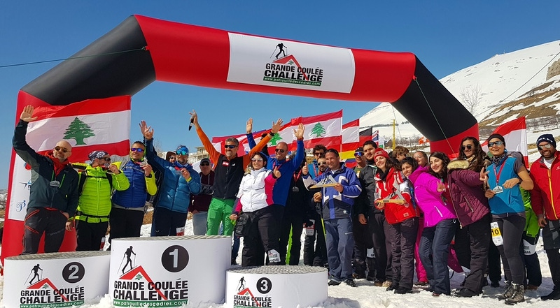 shows a large group of people celebrating on the finish line of a winter sports challenge