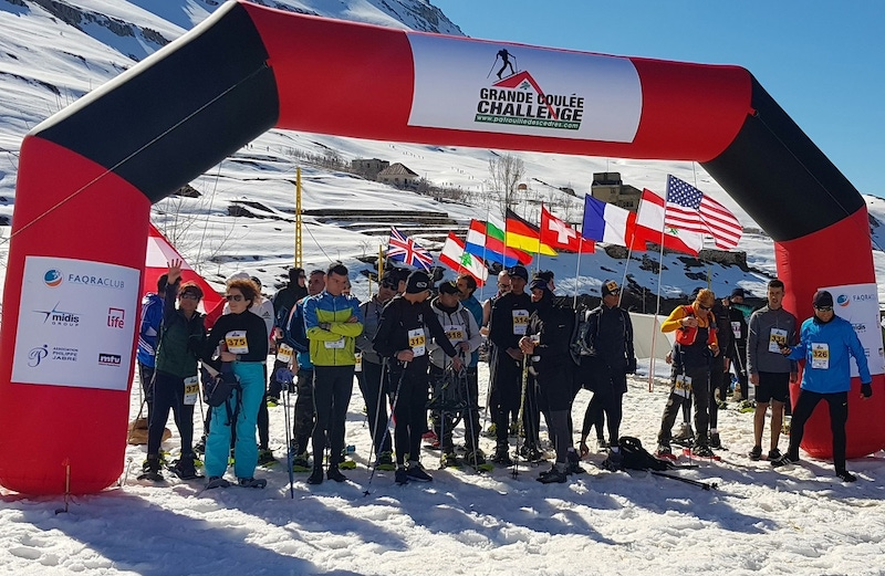 shows a start-line of an outdoor winter sports activity with people ready to ski