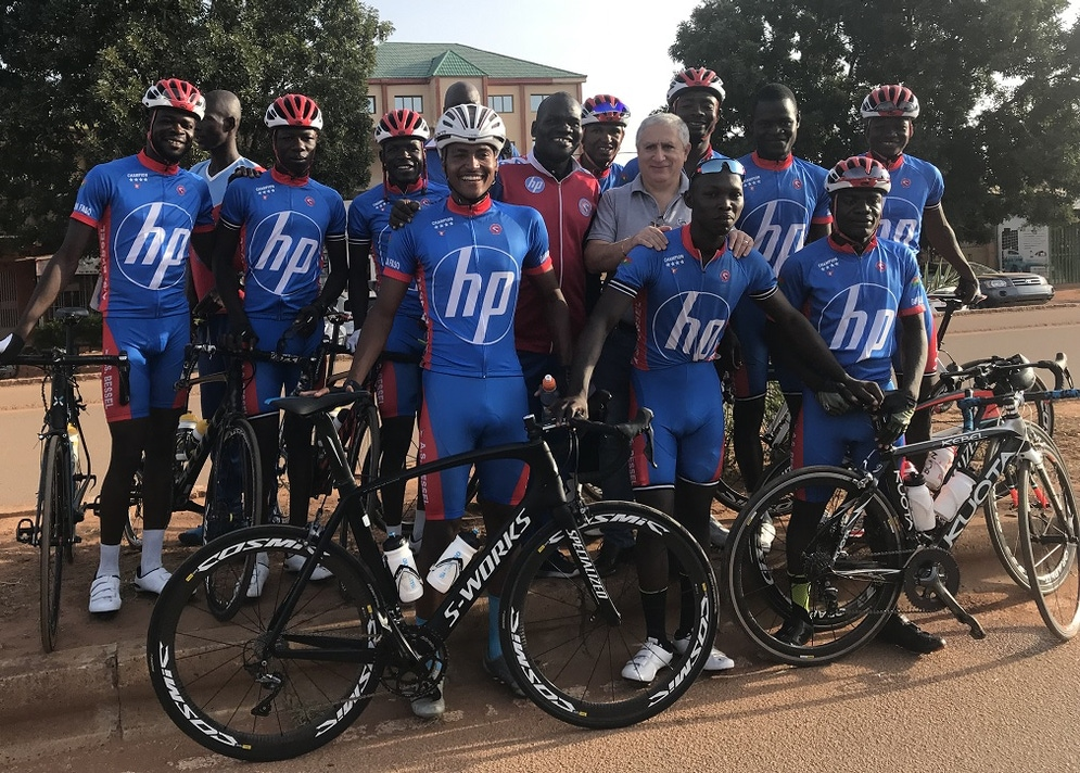 shows a cycle racing team in a group with their bikes