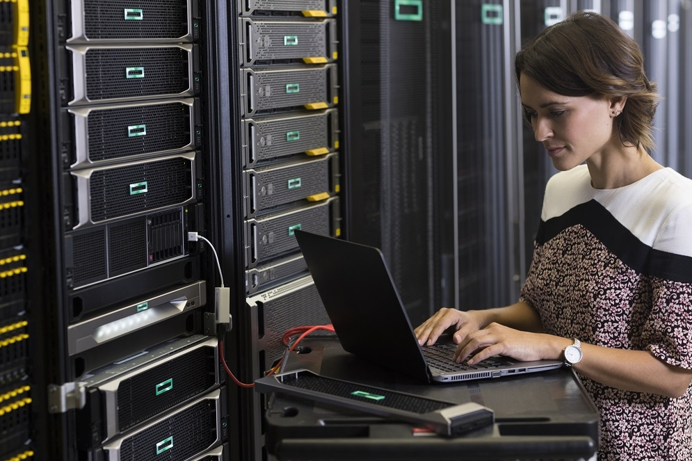shows a woman holding a laptop plugged into a server