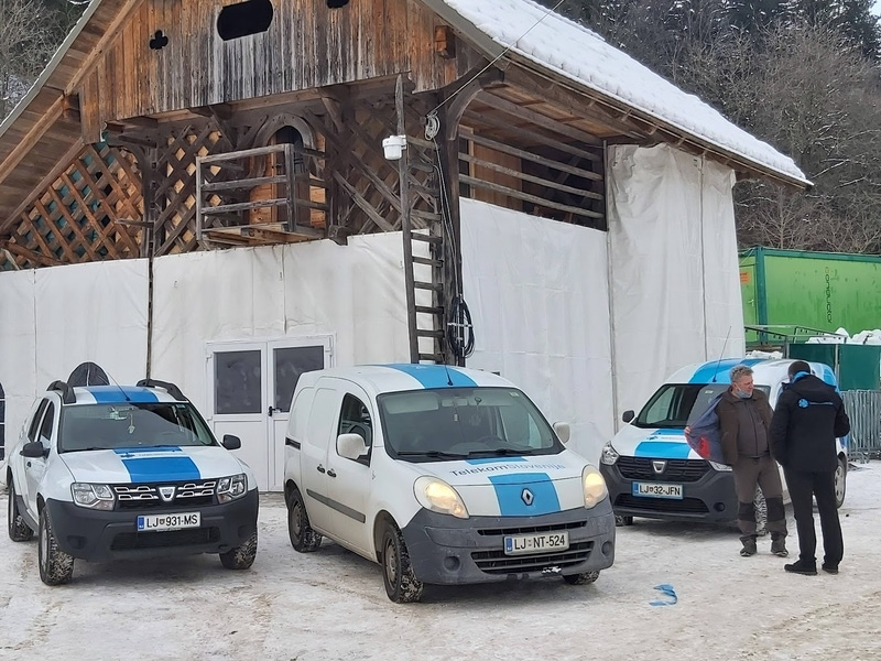three vans and two men are seen outside a snow-covered building