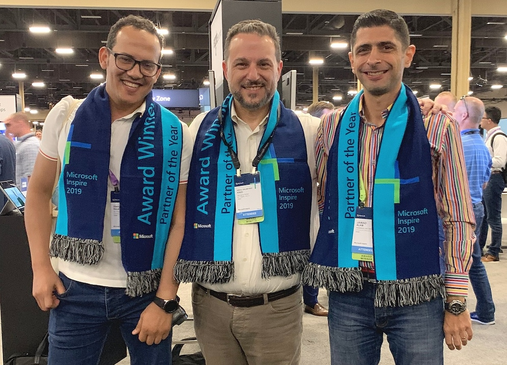 Photo shows three men standing together wearing sashes with the words Partner of the Year written on them