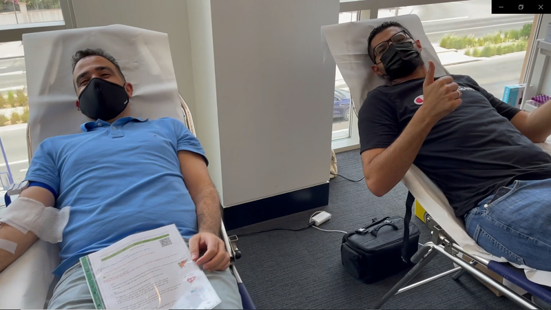 two men recline side by side to give blood