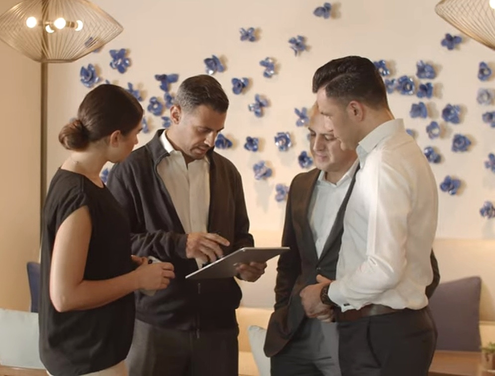 shows a group of people working together around a tablet device