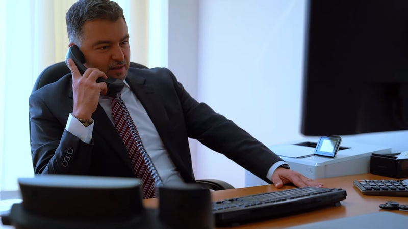 shows a man at a desk speaking into a telephone wearing a suit.
