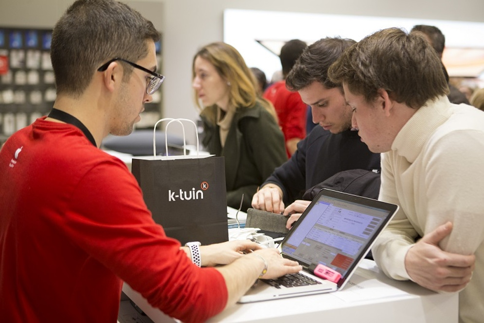 shows a man in the foregound wearing a red t-shirt showing a laptop to two people