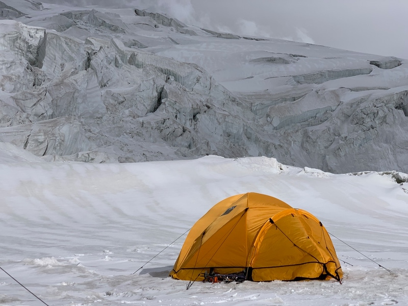 Shows a tent on it's own on a mountainside with nothing but snow around it