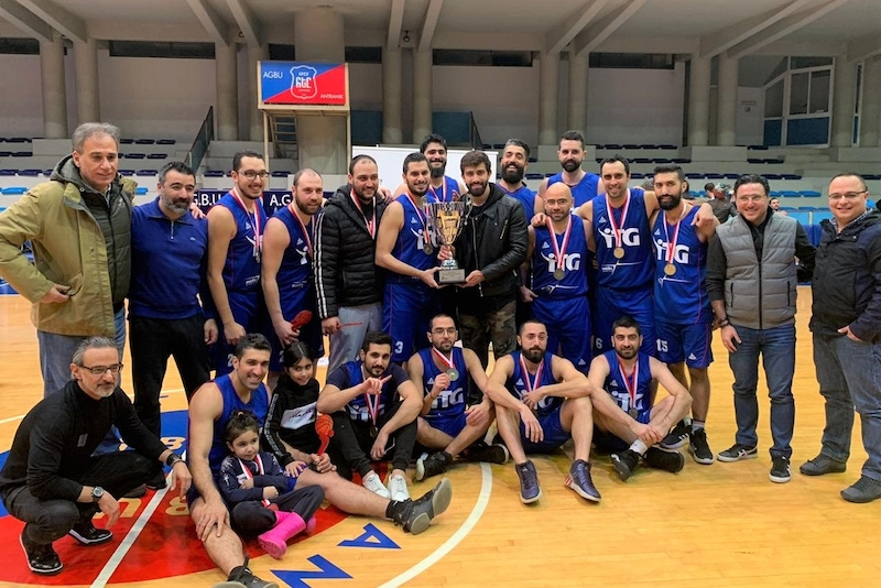 shows a group of men in sports kit smiling with a trophy