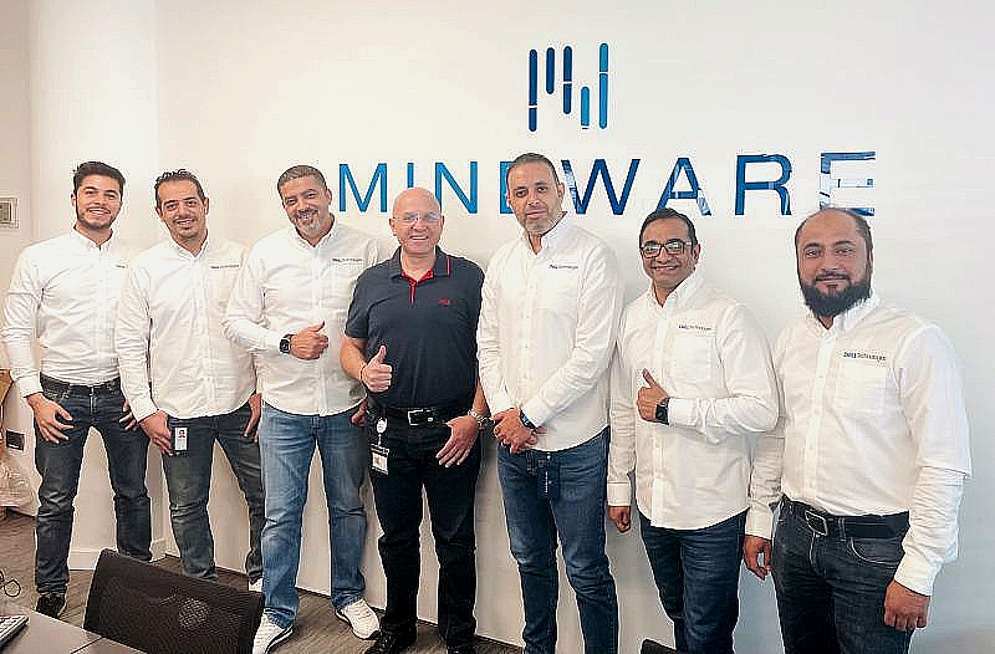 shows a group of men smiling with a backdrop spelling the word Mindware