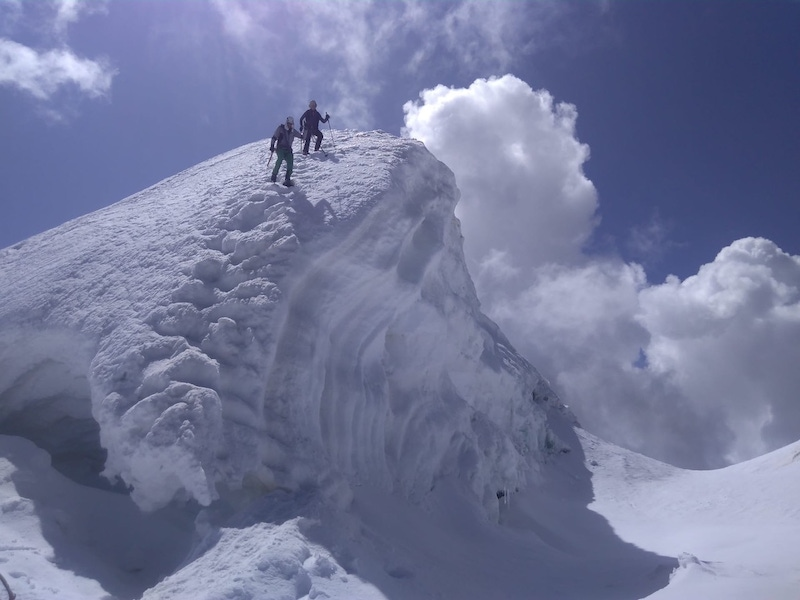 shows two people on a snow-covered peak