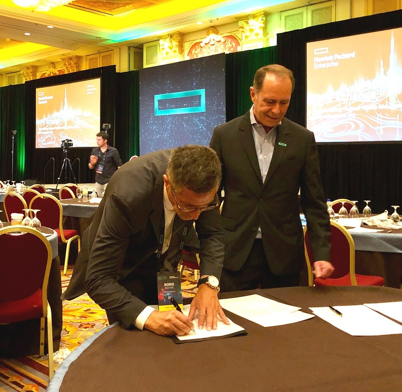 two men signing a document at a table