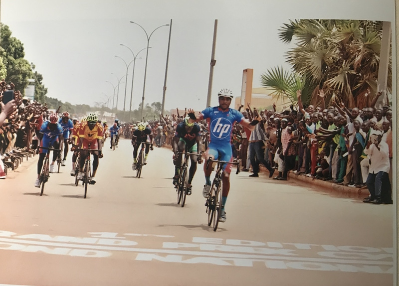 shows a man on a racing bike crossing the finish line