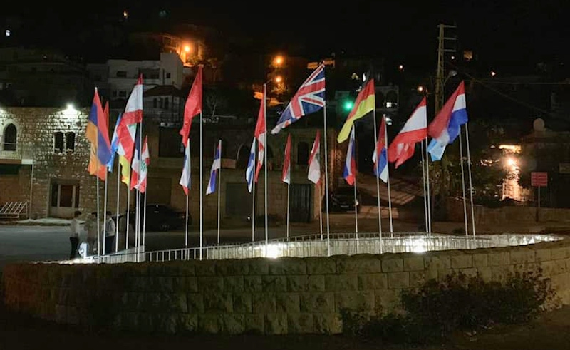shows a group of flags flying in front of a building