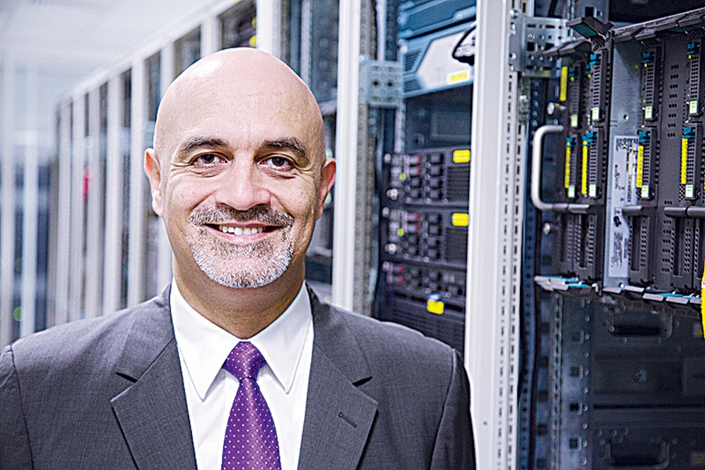 shows a man in a grey suit and purple tie smiling at the camera whilst standing next to a server stack