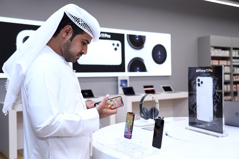 shows a man inspecting an iPhone on a white display stand.