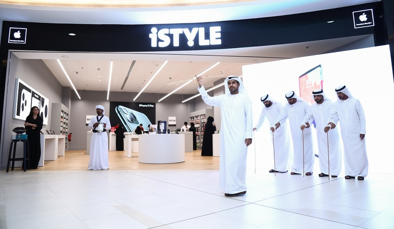 shows a group of men outside the new iSTYLE store in Al Ain