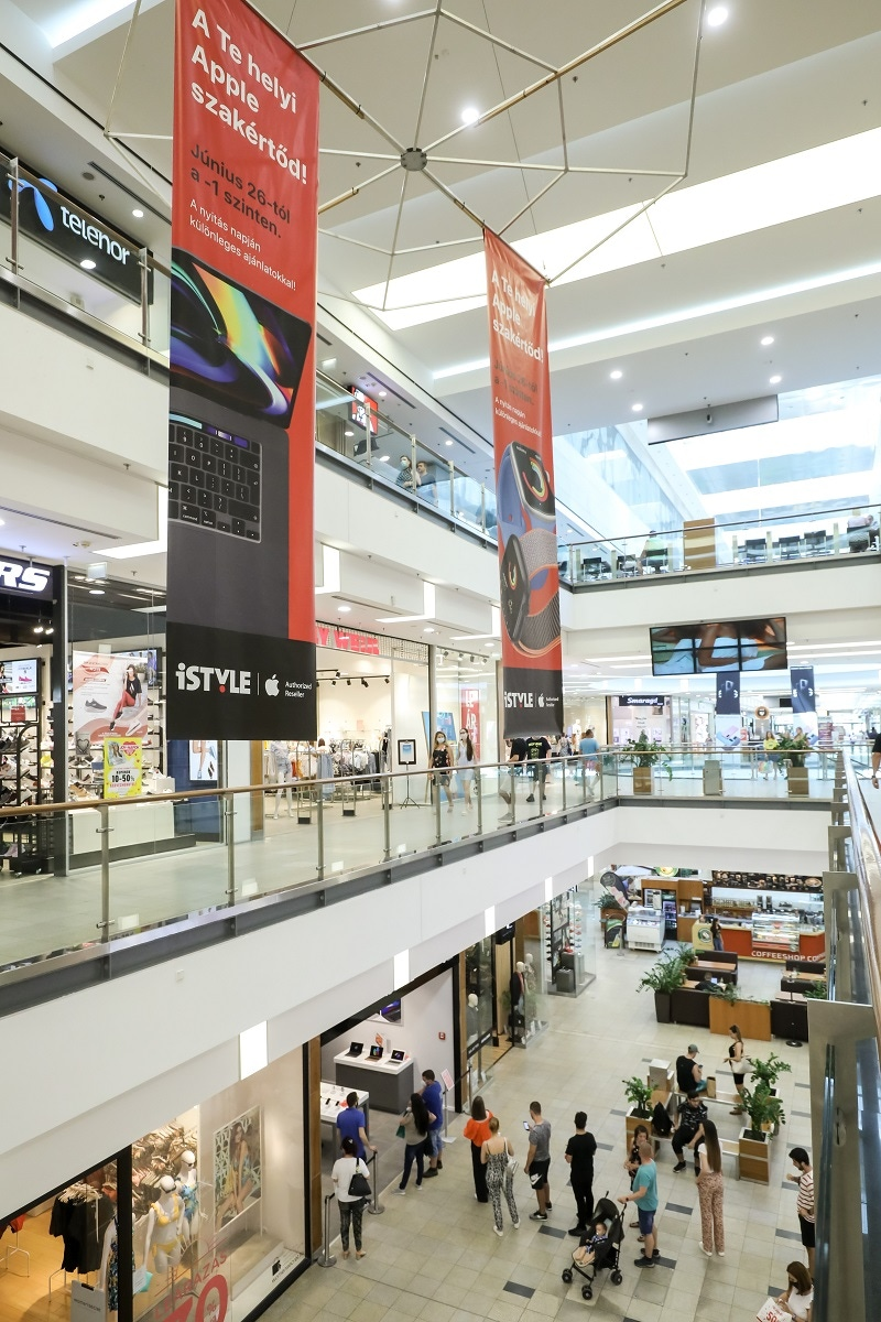 shows a large shopping mall with an iSTYLE banner hanging from the ceiling.