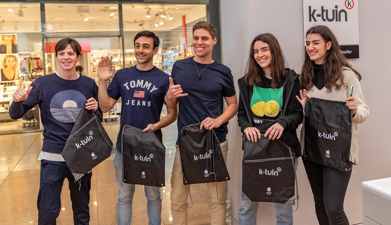 shows a group of people holding goody bags and smiling